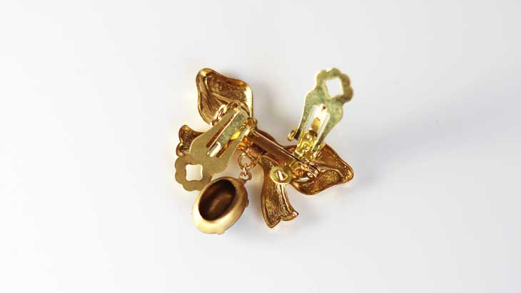 Photo sandwiching a brooch with earrings parts