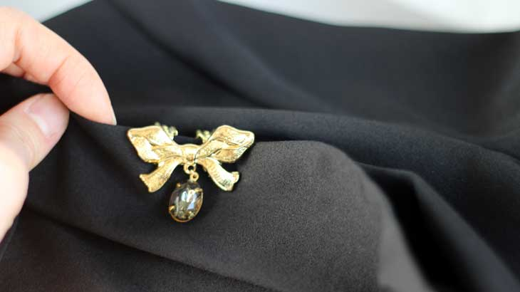 Photo sandwiching a brooch with earrings parts2